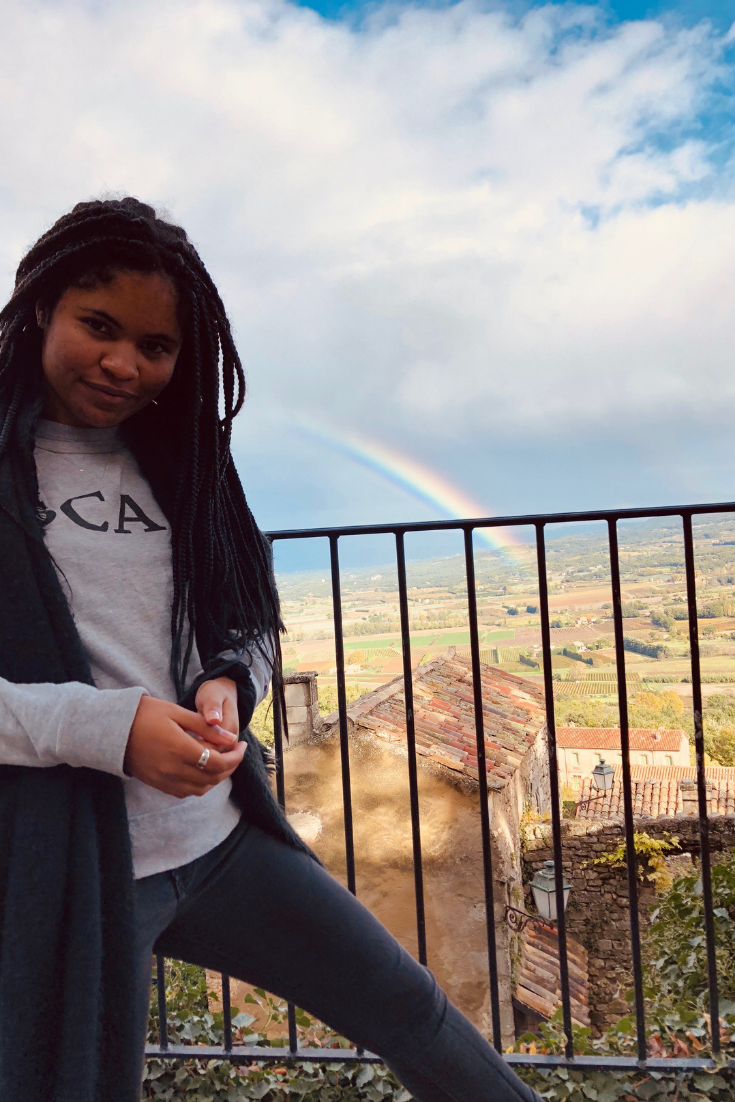 image: girl with braids looking at the camera as she poses in front of a double rainbow