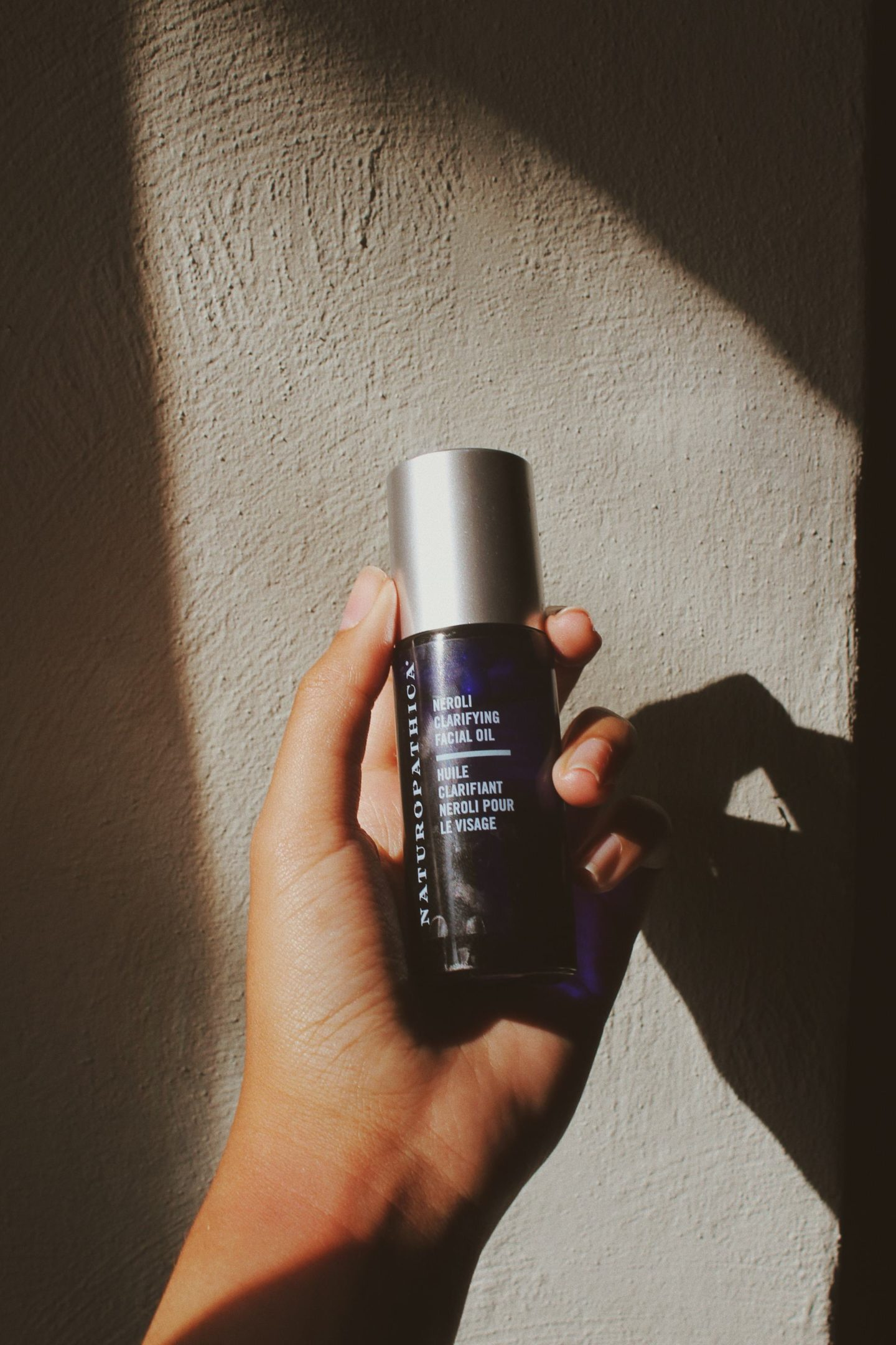 Naturopathica Neroli Clarifying Facial Oil held against a wall