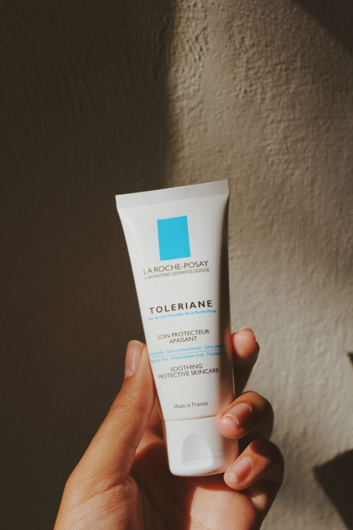 Toleriane Cream held in a hand against a wall