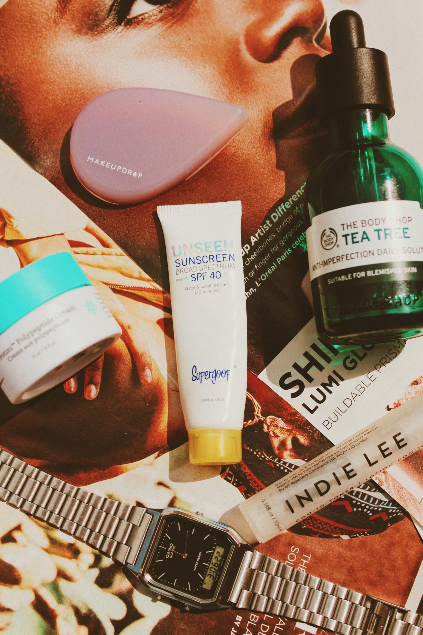 a close up shot of Supergoop Unseen Sunscreen, The Body Shop Tea Tree Anti-Imperfection Daily Solution, Indie Lee CoQ-10 Toner, MakeupDrop Applicator, Drunk Elephant Protini Polypeptide Cream, Casio Silver Watch